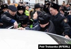 Полицейские насильно сажают в автомобиль журналистку Ингу Иманбай. Алматы, 22 февраля 2020 года.