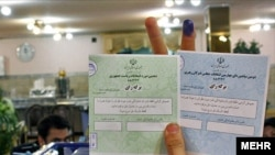 An Iranian voter holds up her ballot at a polling station in Tehran on June 12.