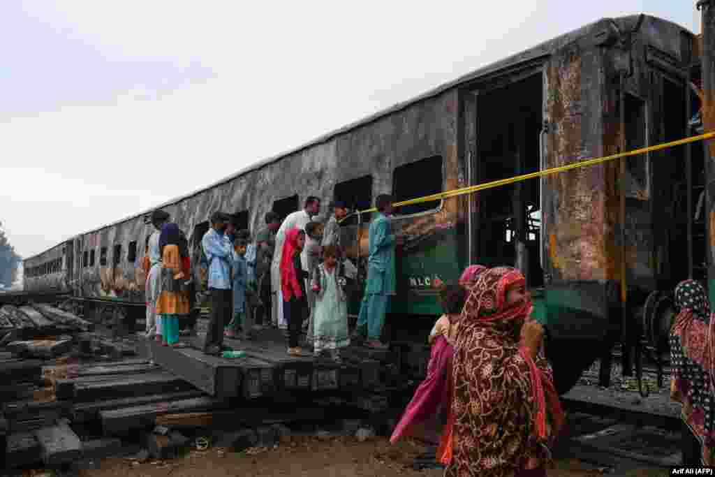People look at burnt-out carriages a day after a passenger train caught fire in Rahim Yar Khan, Pakistan, killing dozens of people. (AFP/Arif Ali)