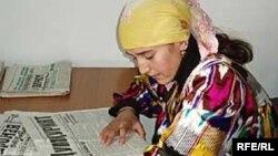 Молодая женщина в национальной таджикской одежде читает газету.