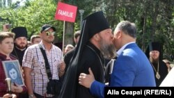 Moldovan President Igor Dodon (right) greets an Orthodox bishop during an anti-LGBT march in Chisinau on May 12.