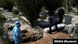 Relatives bury journalist Abdollah Zavieh, who passed away due to coronavirus disease (COVID-19), at Behesht Zahra cemetery in Tehran, March 24, 2020