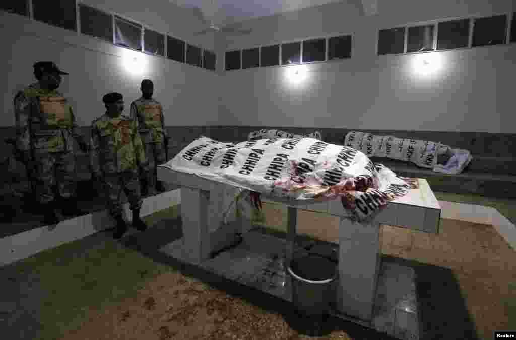 Soldiers from the Pakistani Rangers force stand next to the bodies of their colleagues who were killed in a bomb explosion in Karachi. An explosion near a checkpoint killed four security personnel and injured at least four others. (Reuters/Akhtar Soomro)