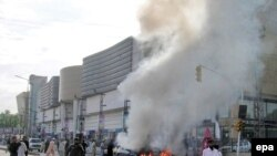 Flames rise from a vehicle outside the paramilitary force Frontier Constabulary headquarters in Peshawar on August 4.