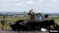 Украина үкіметінің сарбаздары қираған танкіні тексеріп жүр. Славянск, 5 шілде 2014 жыл.