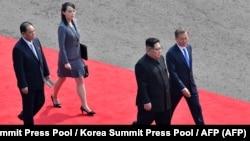 Лидер Северной Кореи Ким Чен Ын (2-й справа) идет с президентом Южной Кореи Мун Чжэ Ином (справа), за ним идет сестра и близкий советник Ким Ё Чжон (2-я слева) по красной ковровой дорожке к зданию Дома мира на официальном саммите. 27 апреля 2018 года.