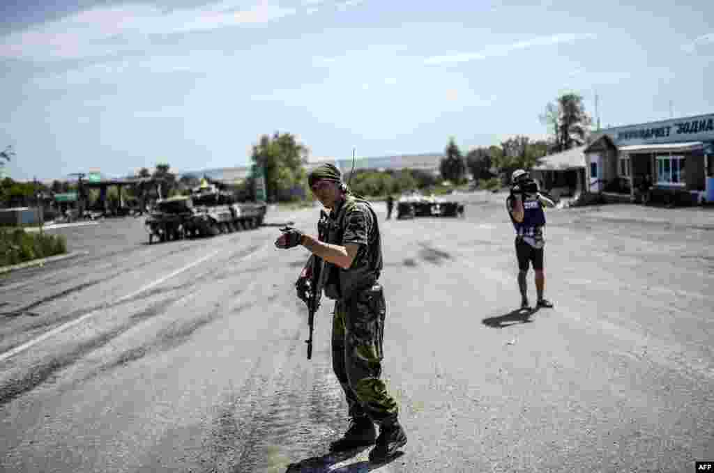 A Ukrainian soldier gestures as he directs traffic at a checkpoint in the village of Debaltseve in the Donetsk region of eastern Ukraine on July 31. (AFP/Bulent Kilic)