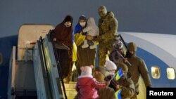 Women and children assisted by Ukrainian personnel disembark from a plane upon their arrival from Syria at an airport outside Kyiv in a photo released on January 1.