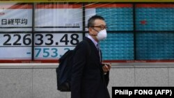 شهروند ژاپنی اواخر فوریه سال جاری در توکیو در حالیکه تابلوی پشت سر او وضعیت بازار بورس را نشان میدهد