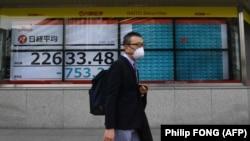 Пішохід у масці проходить повз екран, який показує індекс Токійської біржі, Японія, 24 лютого 2020 року