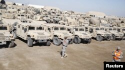 U.S. soldiers check military vehicles to be shipped as troops prepare to pull out of a military base in Nassiriya, Iraq.