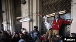 Protestçiler Tahrir meýdançasynyň golaýyndaky hökümet edarasynyň derwezesini böwetleýärler, Müsür, Kair, 11-nji dekabr, 2012
