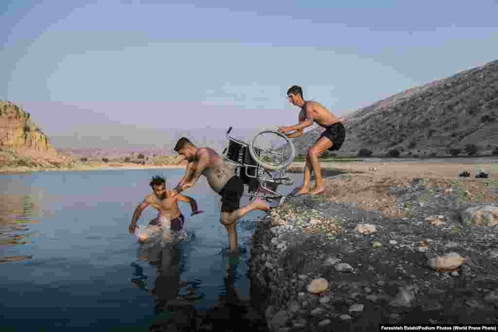 Саид Рамин с друзьями на озере (9 сентября 2020). Профессиональный паркурщик из Ирана, Рамин семь лет назад повердил спинной мозг во время соревнований. Третье место в категории «Фоторепортаж», автор – Ферештех Эслахи