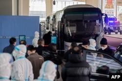 Anëtarët e OBSH-së, që do të hetojnë origjinën e COVID-19, hypin në një autobus, pasi kanë arritur në aerportin e Vuhanit. 14 janar, 2021.