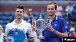 Novak Djokovic of Serbia (left) and Daniil Medvedev of Russia celebrate with the finalist and championship trophies, respectively, after their match in the men's singles final of the U.S. Open on Sept. 12 in New York.