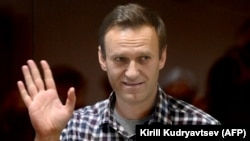 Aleksei Navalny waves from inside a glass cell during a court hearing in Moscow on February 20.
