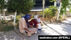 Türkmenistan, çagalary bilen köçede dilegçilik edýän aýal