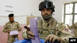 An Iraqi Army commando casts his ballot for the provincial elections at a polling station in the southern city of Basra on April 13.