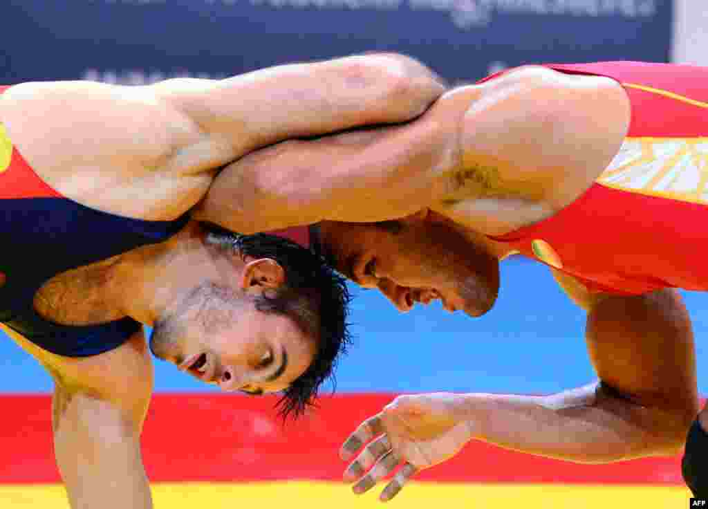 Iran's Ehsan Lashgari (right) fights for the bronze medal with Spain's Talmuraz Friev during the men's freestyle 84-kilogram category at the FILA World Wrestling Championships in Budapest. (AFP/Attila Kisbenedek)