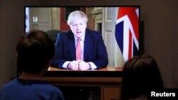 Ұлыбритания премьер-министрі Борис Джонсонның карантин жариялау туралы мәлімдемесін көріп отырған екі бала. 23 наурыз, 2020 жыл.