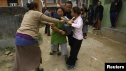 A Tibetan woman is stopped by her friends as she tries to self immolate herself after an argument with police personnel during a protest in Kathmandu in November 2011.