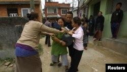 Сябры спыняюць тыбэцкую жанчыну, якая спрабавала падпаліць сябе падчас леташняга пратэсту ў сталіцы Нэпалу, Катманду