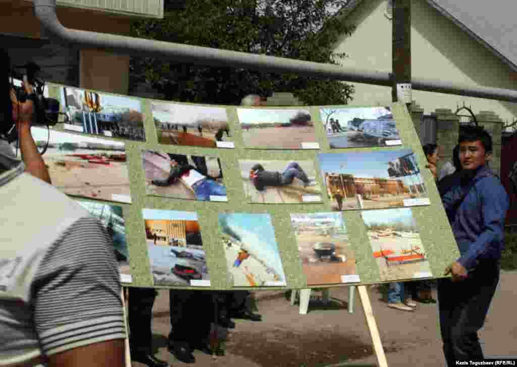 Организаторы фотовыставки переносят щиты с фотографиями. Село Алатау Алматинской области, 15 мая 2012 года.
