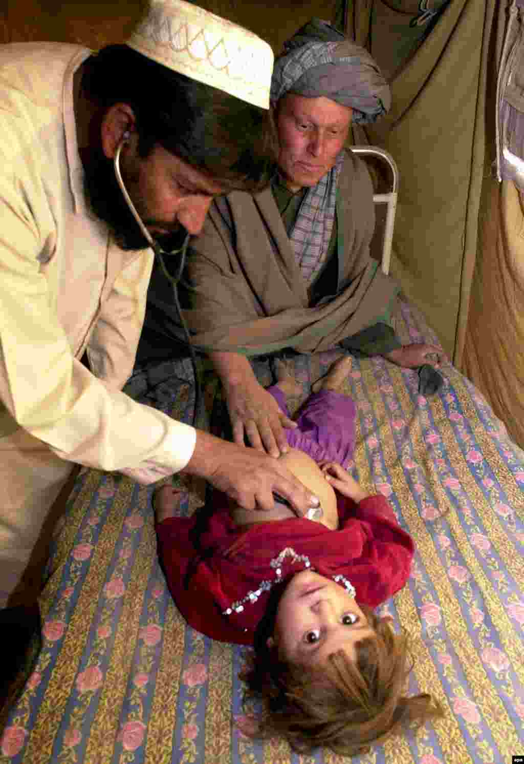 A doctor attends to a sick child who is among the displaced persons in the Afghan border town of Spin Boldak - In 2001, the UN said that more than 3 million Afghan refugees were either in camps (1.2 million) or cities and towns (2 million) throughout Pakistan.
