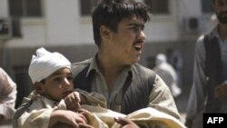 A man carries a wounded child from a Kabul hospital after the latest bombing.