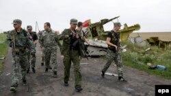 Донецк яқинидаги россияпараст айирмачилар самолёт бўлаклари олдидан ўтиб кетмоқда.