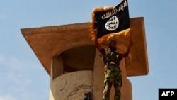 Боевик отряда «Исламское государство Ирак и Леванта» позирует с флагом после захвата позиции армии Ирака. Салахутдин, 11 июня 2014 года.
