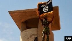 Боевик «Исламского государства» с флагом группировки. Север Ирака, 11 июня 2014 года.