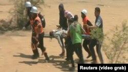 Эпизод противоборства между палестинцами и израильтянами: палестинцы несут раненого. 14 мая 2018