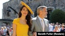 Amal Clooney és George Clooney megérkeznek a Szent György-kápolnához Windsorban Meghan Markle és Harry herceg esküvőjére 2018. május 19-én.
