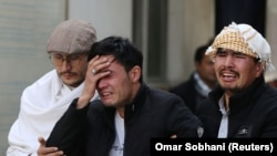 Afghan men cry at a hospital after they heard that their relative was killed during an attack in Kabul on March 6