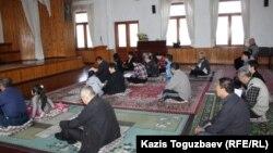 Буддистер ғибадатханасында құлшылық жасап отырған адамдар. Алматы, 7 сәуір 2013 жыл.