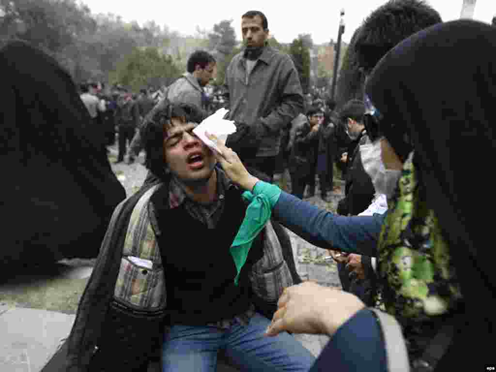 Antigovernment protesters in Tehran help a man injured during a clash with police. - Iranian security forces used batons and tear gas to disperse opposition protesters on December 7. Photo by epa
