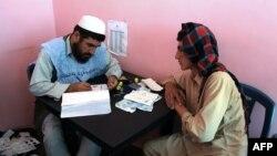 Owganystanyň rayaty saýlawlarda ses bermek üçin registrasion kartyny alýar, Ghazni, 17-nji sentýabr, 2013.