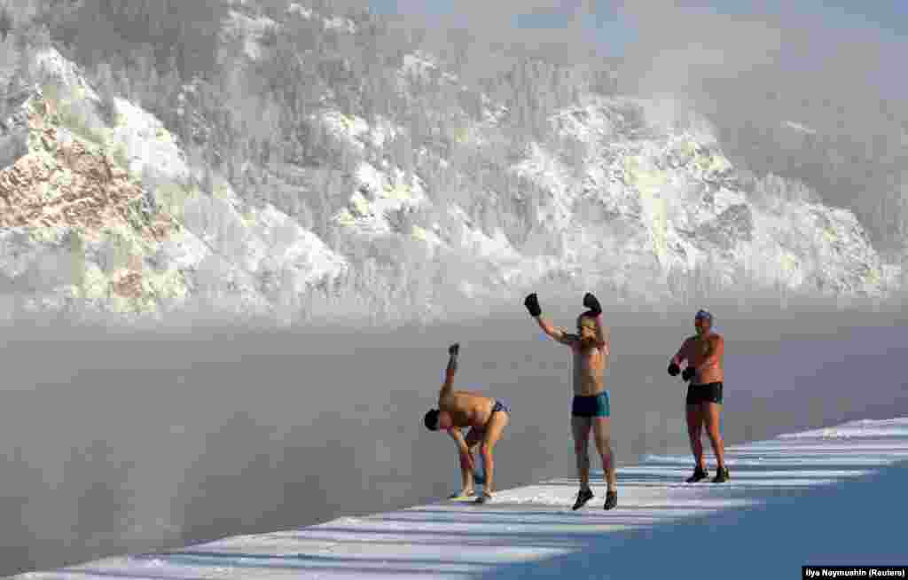 Members of the Dolphin winter swimming club warm up on an embankment of the Yenisei River ahead of their weekly bathing session, with the air temperature at about minus 28 degrees Celsius, in the Siberian town of Divnogorsk. (Reuters/Ilya Naymushin)