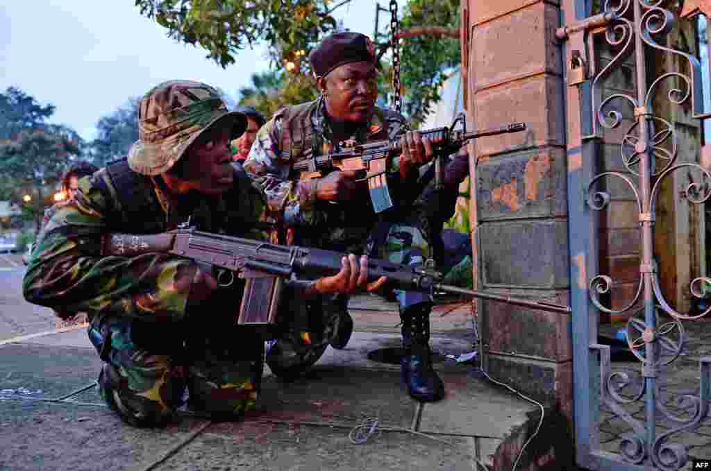 Soldiers take cover after heavy gunfire is heard from the scene of the attack.