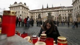 A girl lights candles in front of Prague Castle to bid farewell to former President Vaclav Havel during a funeral ceremony on December 23.