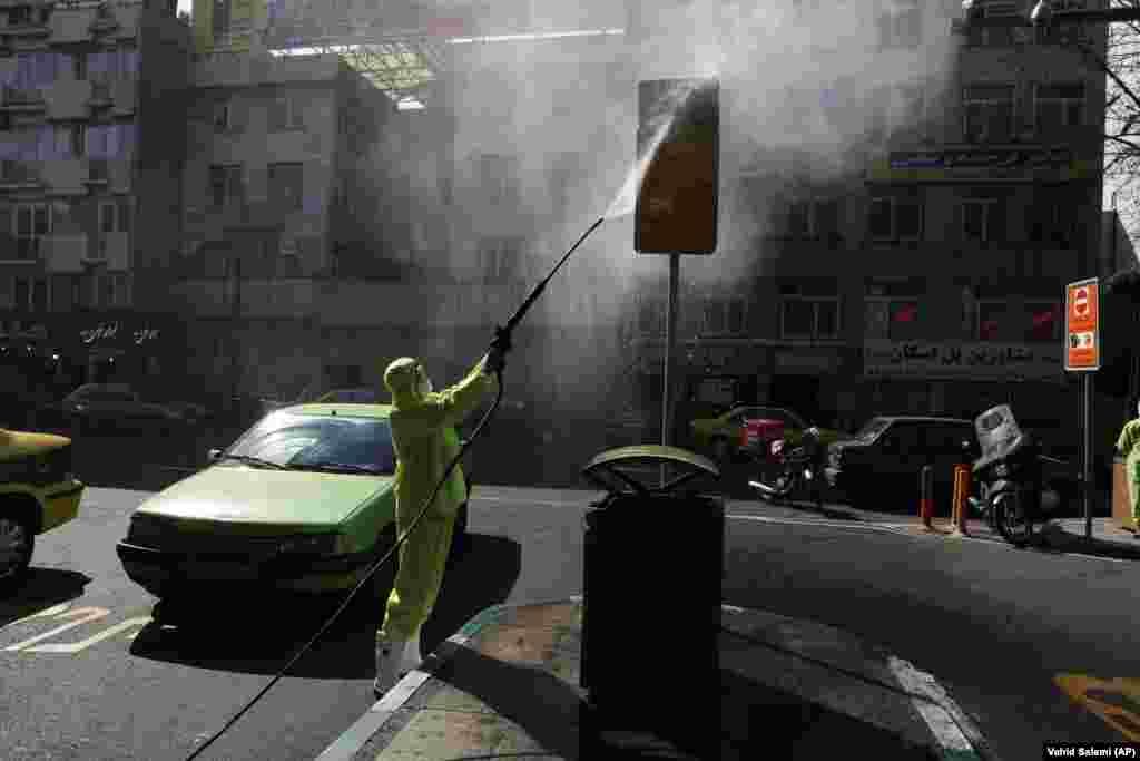 A city worker disinfects a bus stop against the new coronavirus in Tehran. Iran has one of the highest death tolls in the world from the new coronavirus outside of China, the epicenter of the outbreak. (AP/Vahid Salemi)
