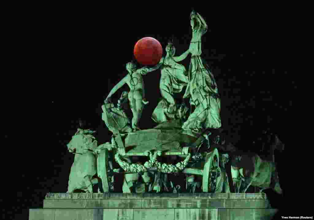 "The moon is seen beside a quadriga on the top of the Cinquantenaire arch during a total lunar eclipse, known as the ""Super Blood Wolf Moon,"" in Brussels on January 21. (Reuters/Yves Herman)"
