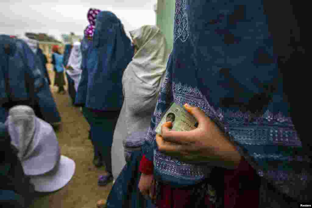 Afghan women wait in line to cast their ballots at a polling station in Mazar-e Sharif on April 5. Voting began in Afghanistan's presidential election, which will mark the first democratic transfer of power since the country. (Reuters/Zohra Bensemra)