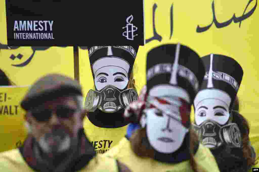 Activists supporting the human rights watchdog Amnesty International wear masks featuring Egypt's Queen Nefertiti wearing a gas mask as they demonstrate near the Chancellery where Germany's chancellor was to meet with Egypt's president in Berlin. (AFP/Odd Andersen)