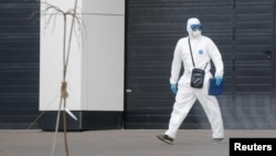 A medical specialist wearing protective gear walks outside a hospital for patients infected with the coronavirus on the outskirts of Moscow on March 23.