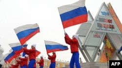 Performers wave Russian flags near the Sochi 2014 countdown clock just outside the Kremlin in Moscow in February 2013, a year ahead of the Games.