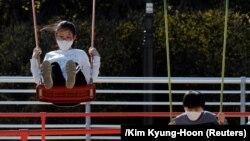 Deca sa zaštitnim maskama se igraju u parku u južnokorejskom gradu Daegu 14. marta