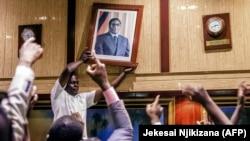 Портрет Мугабе снимают со стены после отставки президента. 21 ноября 2017 года.
