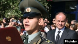 Armenia -- Defense Minister Seyran Ohanian (R) looks on as a military academy graduate takes an oath of allegience to the armed forces.